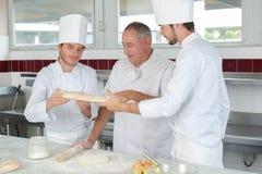Padeiro e assistentes que trabalham na cozinha imagens de stock royalty free