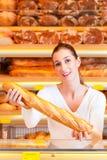 Padeiro fêmea em sua padaria com baguette Imagem de Stock