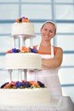 Padeiro feliz Lady que sorri na frente de seu bolo de casamento enrugado Fotografia de Stock Royalty Free