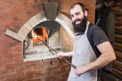 Padeiro masculino que cozinha o forno para cozinhar e agitado os carvões com o pôquer foto de stock royalty free