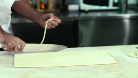 Padeiro que corta a massa para croissant filme