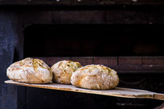 Padeiro que coze o pão feito a mão fresco na padaria fotografia de stock
