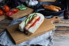 Padella con la salsiccia e le verdure fritte su una tavola di legno Immagini Stock Libere da Diritti