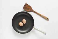 Padella e spatola ed uova su fondo bianco Fotografie Stock Libere da Diritti