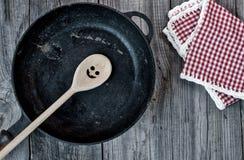 Padella nera della ghisa con un cucchiaio di legno su un gray di legno Fotografia Stock