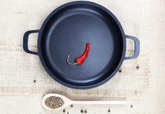 Padella nera della ghisa, cucchiaio di legno, peperoni roventi e PS Fotografia Stock