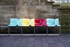 PADERBORN, GERMANY, MARCH 13, 2017: bench with colorful designer. Chairs from plastic on the road in front of a wall of old dark sand stone Stock Image