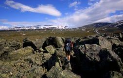 Padjelanta national park. Mountain covered with snow in padjelanta national park in sweden and the hiker passing through big rocks Stock Photos
