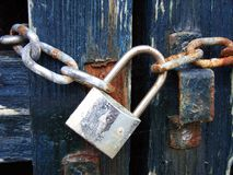 Padlock. Metallic Padlock on a chain closing a blue wood barrier Royalty Free Stock Photography