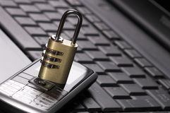 Padlock ad mobile phone on laptop Royalty Free Stock Photos