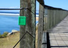 Padlock as symbol of love bond and strong relationship. Padlock on metal wire as symbol of love and bond. Green padlock locked on fence. Concept of strong stock image