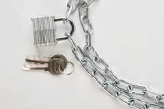 Padlock attached to silver chain. Royalty Free Stock Photos