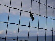 Padlock attached to a wire mesh fence. Viewed in silhouette against a cloudy blue sky Royalty Free Stock Photos