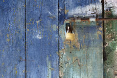 Padlock on bolted blue door. Detail of padlock on bolted door made of rough wooden planks with surface of peeling blue paint royalty free stock photo