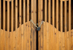 Padlock with chain. Closed wooden door with ornamental barricade and padlock stock image