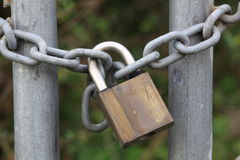 Padlock on chain close-up. Close-up of a chain affixed on two iron rods, locked with a padlock Stock Photo