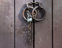 The padlock on the chain closed the old door. Old heavy wooden door painted in brown paint and door handles in the form of massive rings are locked on a rusty royalty free stock image