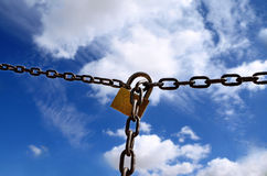 Padlock and chain - horizontal. Padlock on a rusty chain in the middle of the field against the blue sky and white clouds royalty free stock image