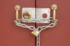 Padlock and chain linking two doors Stock Photography