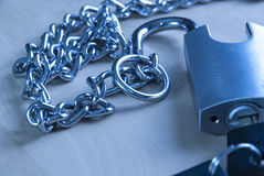 Padlock and chain on wooden table in blue. Close up photo Royalty Free Stock Photo