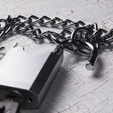 Padlock and chain on wooden table. In blue, close up photo, close up photo Stock Images