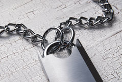 Padlock and chain on wooden table. Close up photo Stock Image