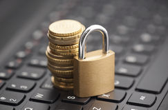 Padlock and coins on laptop keyboard Stock Image