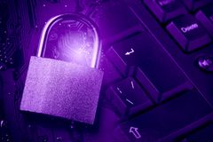 Padlock on computer motherboard and keyboard. Internet data privacy information security concept. Ultraviolet toned image Royalty Free Stock Image