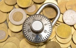 Padlock on Currency coins background security concept Royalty Free Stock Images