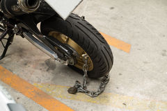 Padlock das Sicherheitsschloss, welches das Motorradrad auf Straße blockiert Stockfoto