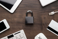 Padlock and different gadgets on the wooden office table Royalty Free Stock Photo