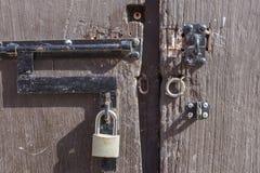 Padlock e metal gli anelli sulla porta di legno rustica sbloccata Immagini Stock