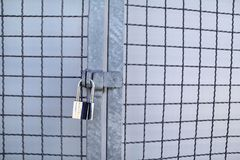 Padlock em uma cerca de chainlink/chave mestra e em uma corrente oxidada velha com gaiola de aço, acima do fim/fechamento fechado fotografia de stock royalty free