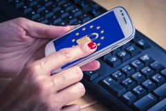 Padlock and EU flag on smartphone screen, GDPR metaphor. Padlock and EU flag on smartphone screen and female hands using it. Suitable for the EU General Data Royalty Free Stock Photo