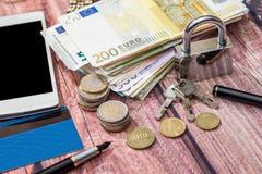 Padlock with euro coin and euro banknotes. Notepad, calculator Stock Photo