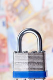 Padlock in focus on a background of money. Padlock in focus with a background of out of focus bank notes Royalty Free Stock Image