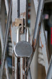 Padlock on a Gated Store Front. A closed store front gated shut and padlocked Stock Photos