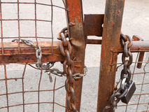 Padlock with heavy chain. Padlock and chain on a metal industrial gate Royalty Free Stock Images