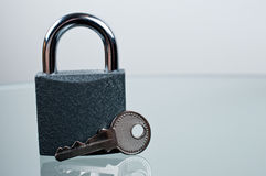 Padlock with a key on desk. Padlock with a key on grey background Royalty Free Stock Image