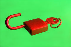 Padlock with key and green background Stock Photo