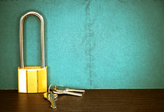 Padlock with key on table with green wall. Royalty Free Stock Photography