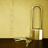 Padlock with key on table with vintage wall. Royalty Free Stock Photos