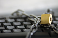 Padlock with metal chain hooked and locked across computer keyboard, internet security concept Stock Images