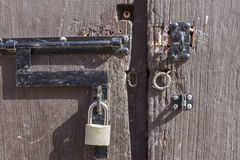 Padlock and metal rings on unlocked rustic wooden door Stock Images