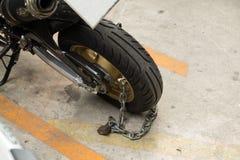 Padlock o fechamento da segurança que obstrui a roda da motocicleta na rua Foto de Stock