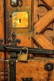 Padlock on old oak Cathedral door, with brass and iron fittings royalty free stock photo