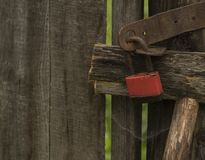 Padlock. Old rusty red padlock on decrepit plank fence Stock Images