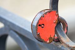 Padlock of red color on an iron fence Royalty Free Stock Photos
