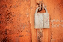 Padlock on a rusty brown metal door. Processed for vintage tone. Effect. Rusted iron orange plate door with handle and lock Stock Photography
