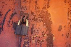 Padlock on a rusty brown metal door. Processed for vintage tone. Effect. Rusted iron orange plate door with handle and lock Royalty Free Stock Photo